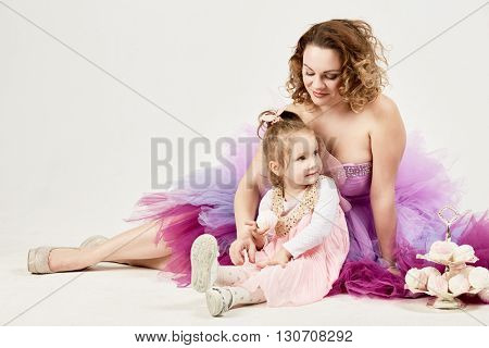 Mother and little daughter sit together on the floor near two-story dish with marshmallows.