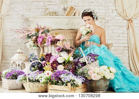 Woman in blue fluffy dress sits on couch in room with mass of flowers sniffing bunch of flowers.