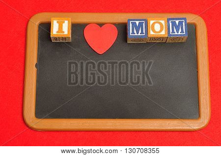 I love mom spelled with colorful alphabet blocks and a red heart on a blackboard