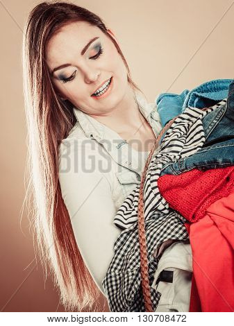 Young Woman Hold Pile Of Clothes.