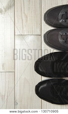A pair of male and female shoes on a wooden floor