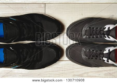 A pair of male and female trainers in front. top view