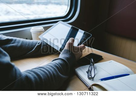 The man sits at a table in a train with a tablet in hands