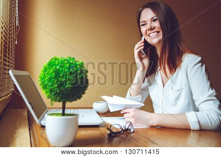 businesswoman in modern office takes a break and prepares a paper airplane