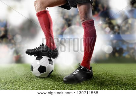 close up legs and feet of football player in red socks and black shoes playing with the ball standing on stadium green grass pitch with background flashes and light flares