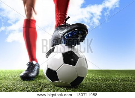 close up legs and feet of football player in red shocks and black shoes posing with the ball standing on grass outdoors isolated on blue sky background