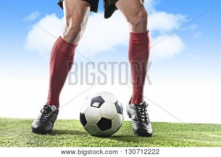 close up legs and feet of football player in red socks and black shoes running and dribbling with the ball playing outdoor on green grass pitch under a blue sky