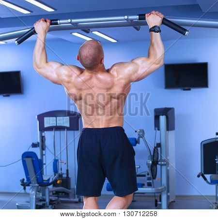 Young man training at gym with exercises .