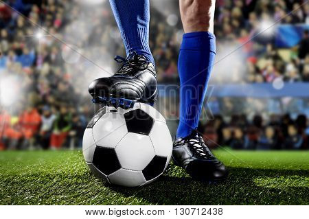 close up legs and feet of football player in blue socks and black shoes standing with the ball playing match at soccer stadium on green grass pitch with audience flash lights and flare