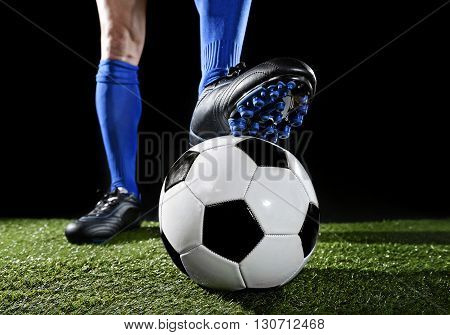 close up legs and feet of football player in blue socks and black shoes standing with the ball playing on green grass pitch isolated on black background