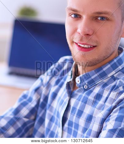 Young businessman working in office , sitting at desk