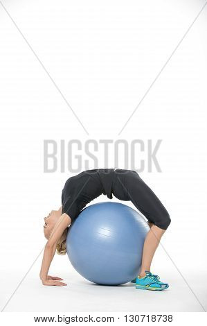 Sportive blonde girl in the sportswear with a blue fitball on the white background in the studio. She wears cyan-yellow sneakers, black pants and black t-shirt. She makes a bridge over the fitball. Photographed sideways. Vertical.
