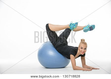 Young blonde girl in the sportswear lies on a blue fitball on the white background in the studio. She wears cyan-yellow sneakers, black pants and black t-shirt. She leans on her elbows and palms, her pelvis is on the fitball, her legs are in the air and b