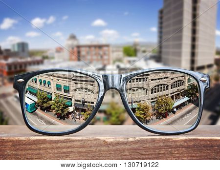 hipster glasses on a park bench or table with a cityscape in the background