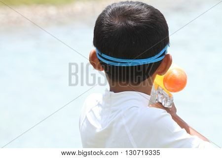 Japanese boy playing with water gun (first grade at elementary school)