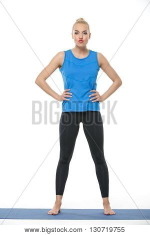 Cute blonde girl in the sportswear stands on a blue gymnastic mat on the white background in the studio. She wears black pants and blue sleeveless t-shirt. She is barefoot. She holds her hands on the waist. She looks into the camera with pouty lips. Verti