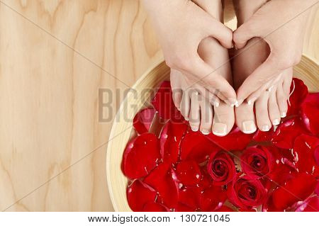 Well groomed female feet and heart shaped hands shot on the wood background with red roses