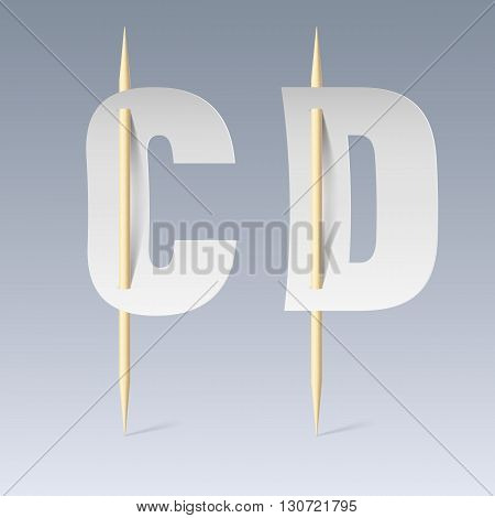White paper cut font on toothpicks on grey background. C and D letters