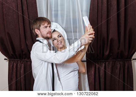 Husband and wife make selfie. Girl with a towel over his head. Marital time. After a night in a hotel.