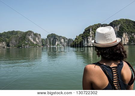 A tourist from the boat staring with amaze at the limestone karsts in Ha Long Bay, Vietnam. Ha Long Bay boats of thousands of limestone karsts like this and is a treat to visit.
