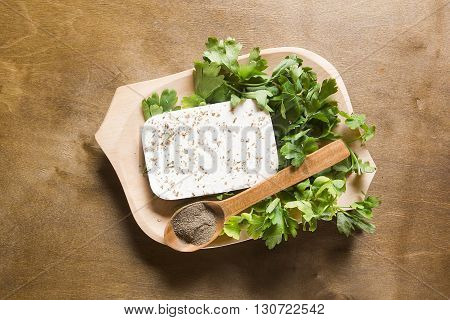 Feta cheese and fresh herbs in a wooden plate on the table