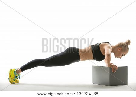 Pretty blonde girl in the sportswear leans on a gray cube while makes the plank on the white background in the studio. She wears yellow-cyan sneakers, mint socks, black pants and black top. She looks at the cube. Photographed from the side. Horizontal.
