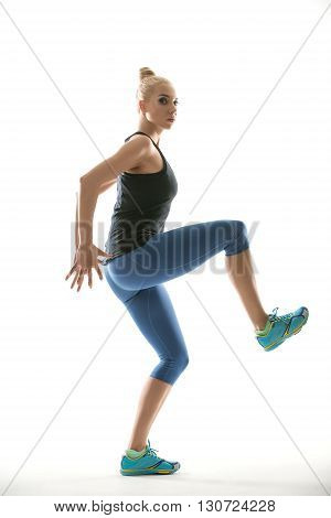 Cute girl in the sportswear stands sideways on the white background in the studio. She wears cyan-yellow sneakers, mint socks, blue pants and black sleeveless t-shirt. Her hands are behind her torso, right leg is in the air. She looks into the camera with