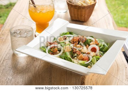 Caesar salad in White plate Orange juice Glass of water placed on wooden table.