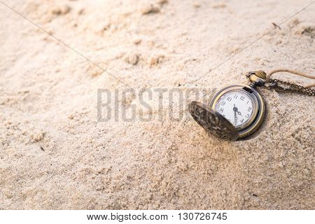 Vintage necklace watch on the sand - concept of time