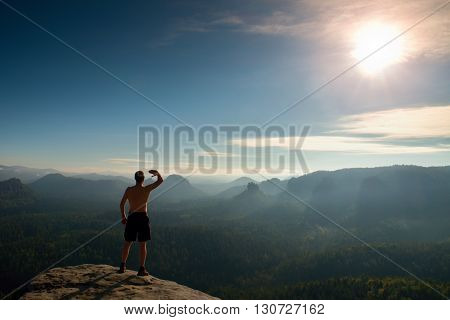 Naked Man In Black Pants Only At Top Of Mountain At Sunset.