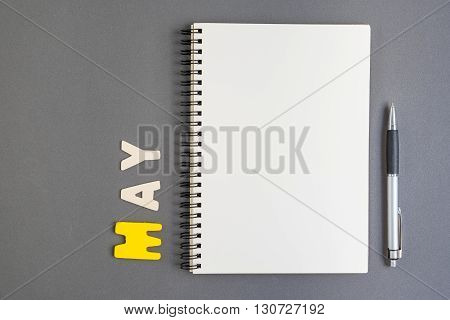 Spiral open notebook with pen and May month wording on grey background