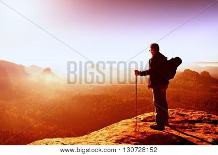 Backpacker With Eyeglasses And Poles In Hand. Sunny Day In Rocky Mountains. Hiker With Big Backpack
