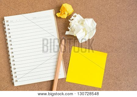 Top view of open spiral notebook empty line paper with brown pencil and yellow sticky notes and crumpled paper ball - notebook paper on brown background
