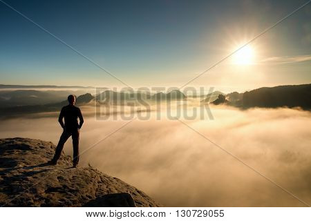 Hiker In Black Stands On Rock Abve Valley Within Daybreak And Watch To Sun. Beautiful Moment The Mir