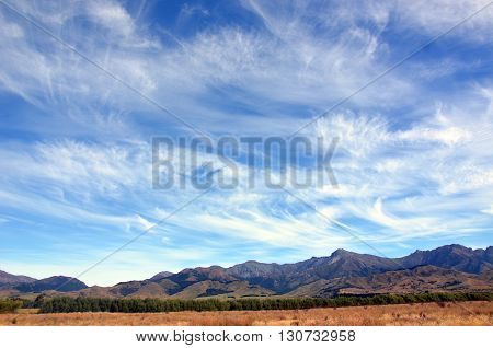 Wispy clouds in blue skies above a rugged mountain range in New Zealand