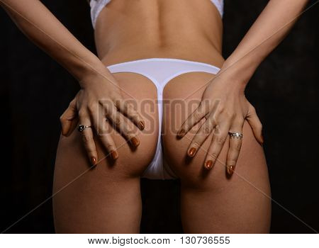 Women's Booty in white panties on a black background of the body part