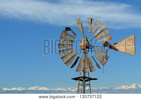 Broken Antique Farm Windmill with Distant Mountains