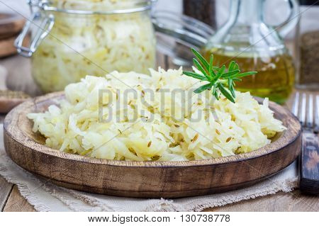 Homemade sauerkraut on a wooden plate, closeup