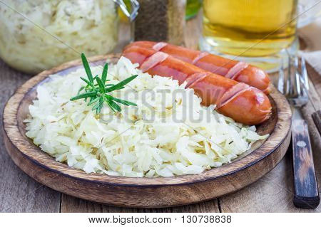 Homemade sauerkraut with sausages on a wooden plate