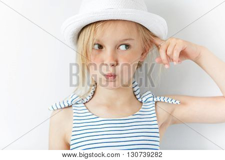 Headshot Of Angry And Irritated Preschool Girl In White Hat And Striped Dress, Gesturing With Index
