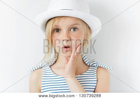 Portrait Of Surprised Or Frightened Girl Looking At The Camera With A Hand On Her Cheek. Close Up Sh