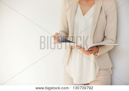 Isolated Portrait Of Young Stylish Woman Wearing Formal Suit, Reading Fashion Magazine And Looking F