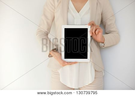 Young Female Holding Tablet Computer Isolated Against White Studio Wall. Businesswoman Showing Table