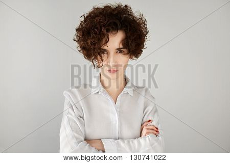 Angry Businesswoman With Brown Curly Hair Looking At Camera With Sceptical And Displeased Expression