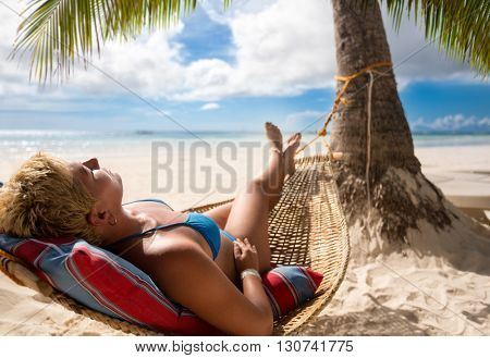 nice woman in hammock in tropical environment