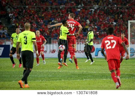 July 24, 2015- Shah Alam, Malaysia: Liverpool's Jordan Henderson (14) challenges an aerial ball in a friendly match against the Malaysian Team. Liverpool Football Club from England is on an Asia tour.