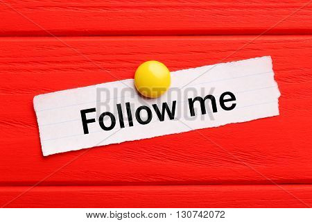 Sheet of paper on red wooden background, follow me