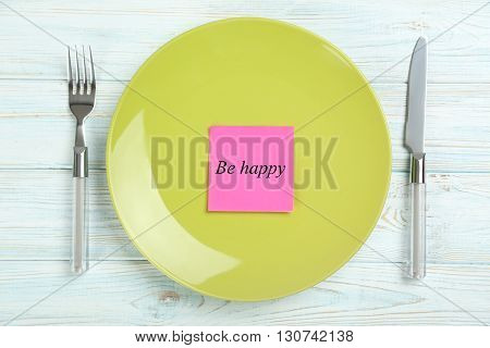 Green plate on a blue wooden table, be happy