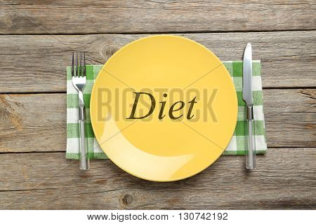 Yellow plate on a grey wooden table, diet