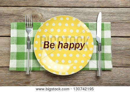 Yellow plate on a grey wooden table, be happy